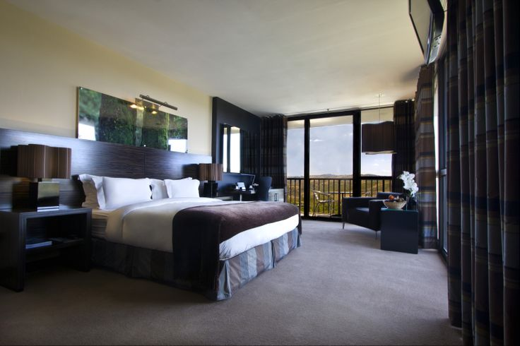 Luxury Bedroom - Black: These suites have large floor to ceiling windows overlooking the rolling landscape of the Klipriviersberg; they are located in the bush area of Thaba Ya Batswana ensuring quiet privacy. Each air-conditioned suite is equipped with large screen LCD television, and iPod docking station.