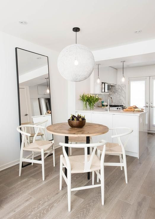 Beautiful eat-in kitchen boasts an eye-catching Moooi Random Light hung over a round wood and iron dining table surrounded by Hans Wegner Wishbone Chairs placed on gray wash wood oak wood floors in front of a black leaning mirror.
