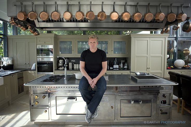 Gordon Ramsey in his kitchen at home in London. Love the finishes in this kitchen. Black honed countertops with a stainless steel island.