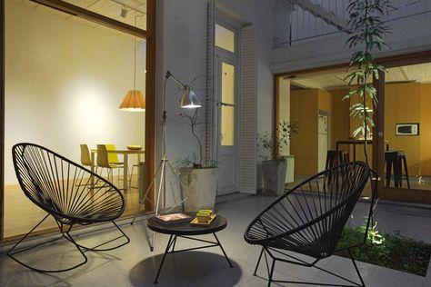 Los ventanales abrieron los ambientes al patio, que es el alma de la casa. Silla 'Condesa' ($1.855) y mecedora 'Acapulco' ($2.300) con estructura metálica negra, mesa ratona, lámpara transportable 'Trípode' con brazo de aluminio ($3.500, todo de Broon) y embutido de piso 'Frog' con lámpara Gu10 led .