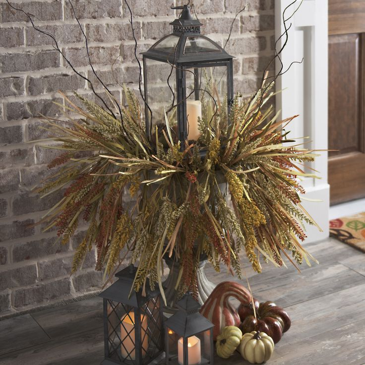 Lanterns are a beautiful way to decorate your front porch for fall! Whether you want to light candles or rely on LED lights, the glow from a lantern can make your home look even cozier. Place it in a planter for a more rustic style!