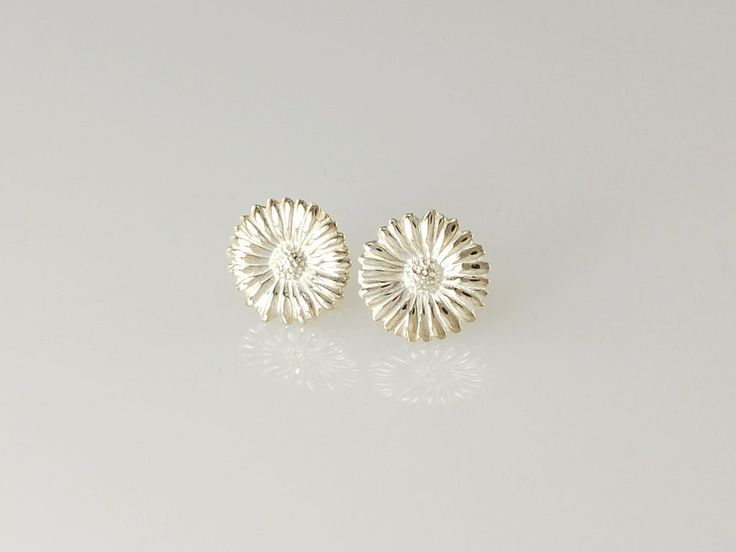 -Daisy Stud Earrings- NZ$89- Silver. Our silver daisy stud earrings are a very popular gift. Do you remember playing the 'love me, love me not game' or maybe you remember sitting in the summer sun creating long daisy chains? Sadly real daisies only last a short time but our silver daisies are everlasting! The daisy collection includes pendants, hoops earrings, studs and the daisy chain necklace. Daisy size - 12.5mm. Jewellery made @jewelbeetle in Nelson, New Zealand.