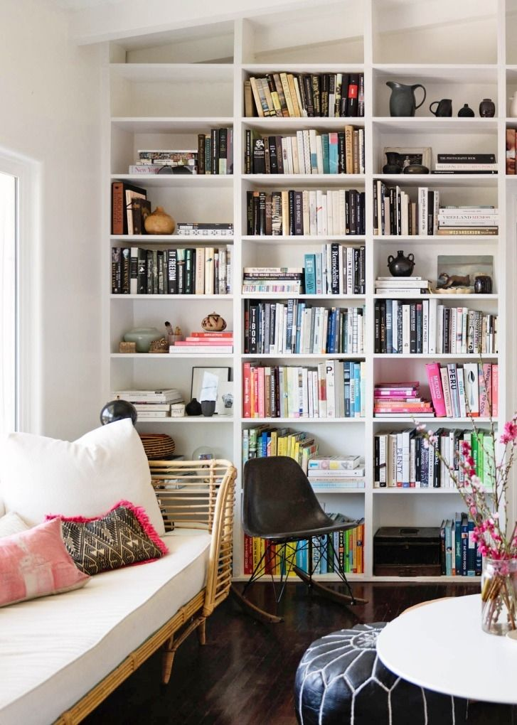 Floor to ceiling open shelving showcases books like art pieces in this home.