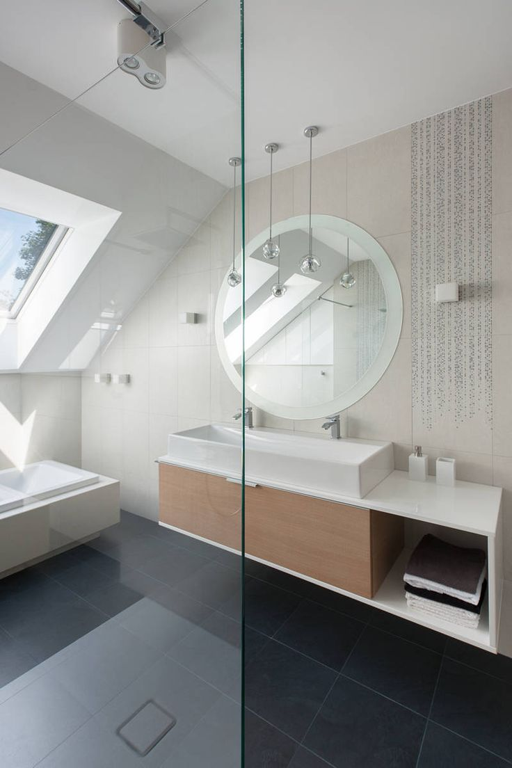Wooden Vanity and Wide Mirror near the White Tub