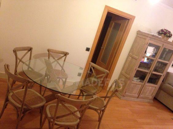 Mesa redonda de comedor, con tablero de cristal y patas cruzadas de madera maciza de pino.