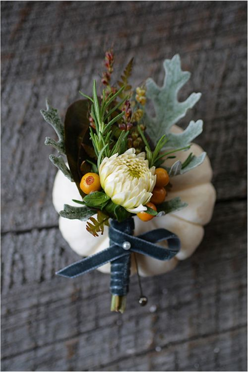 A fall boutonniere with dahlia buds, rosemary, dusty miller, and berries | Brides.com