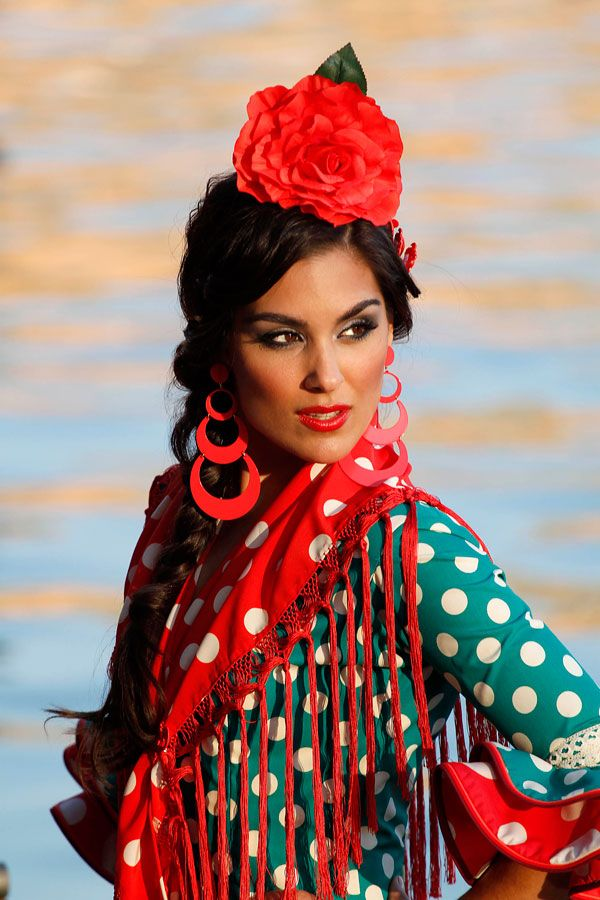 I love the way so many traditional flamenco dresses are done in dots.  The colors are sumptuous in this outfit.  The dancer is a beauty.  I love her face, the dots, the scarf, the fringe, the earrings, the dress, and the huge hair ornament.