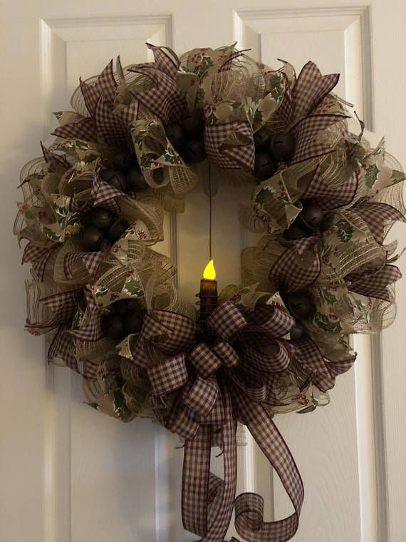 This primitive Christmas Wreath is adorned with rustic jingle bells and has a flickering candle in the center. The wreath is made of poly burlap mesh and accented with burgundy checked ribbon and canvas holly and berry ribbon. Rustic jingle bells in clusters of three adorn this wreath.