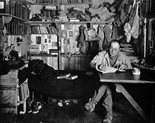 Robert Falcon Scott sitting cross-legged at table, pipe in hand, apparently writing. Much clutter of clothing, books and equipment is in the background.R
