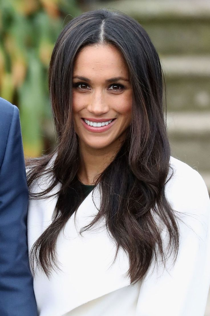 """At a photocall on the day that [link url=""""http://www.vogue.co.uk/article/prince-harry-and-meghan-markle-engaged""""]she and Prince Harry announced their engagement[/link], Markle wore her hair in gently tousled waves, whilst her make-up was simple and natural-looking."""