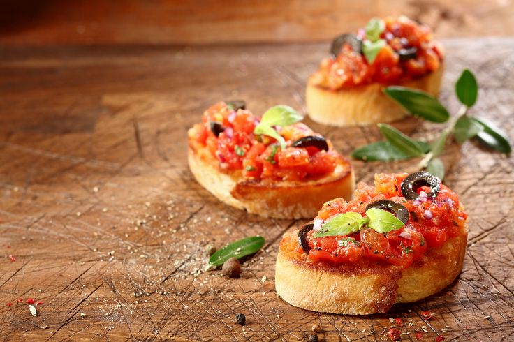 Preparing tasty Italian bruschetta with chopped vegetables and oil on grilled or toasted crusty baguette sprinkled with seasoning and spices on an old grungy scored wooden chopping board #appetizer #canapes #snacks #appetizers #appetizerplatter #appetizerspecial #snacktime #snack #snackporn #rusticfood #rusticstyle #rustic #rusticparty #rusticdinner #vintagedinner #vintagewedding #catering #cateringlife #events #corporateparty   How was your rustic day? #BeLikeTomBeRustic