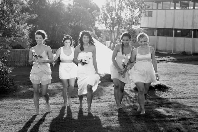 The barefoot bride and her bridesmaids wearing off-white dresses and each holding a single white rose.