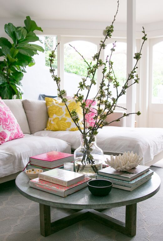 Zinc-top round coffee table with Mangowood timber base, glass vase with flowers/branches, hardcover design books, bowls, coral, Moroccan patterned rug, beige sofa, yellow and pink floral cushions, fiddle leaf fig indoor plant