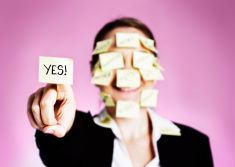 Multitasking woman covered in task labels holds up YES! stock photo