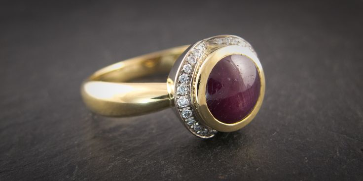 A 5ct Indian Star Ruby set in yellow gold with a white gold and diamond surround