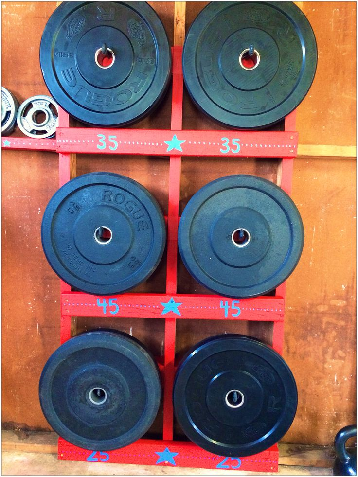 Crossfit home gym. DIY bumper plate rack using studs 4x4's 2x4's and long eye hooks. Paint optional.