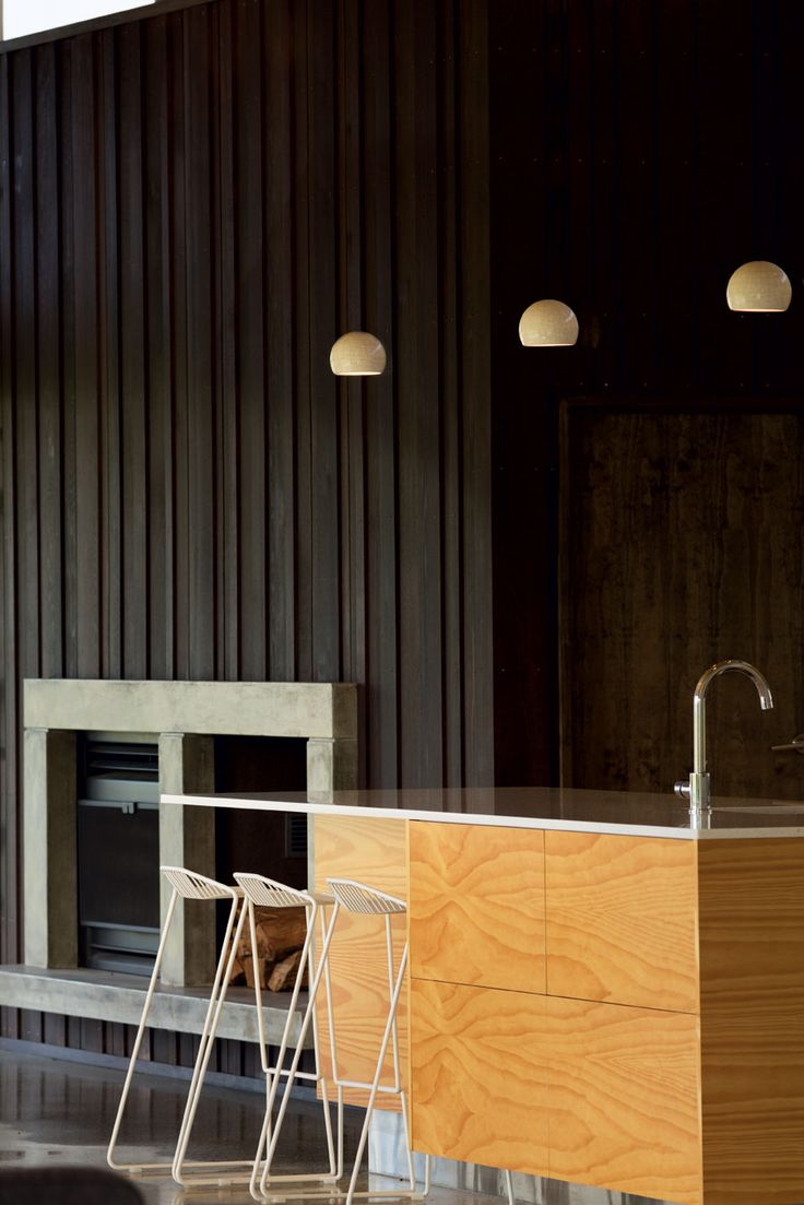 The garage element, clad in vertical shiplap boards, has been inserted into the house extending the external material palette into the interior as a feature surround for the fireplace.