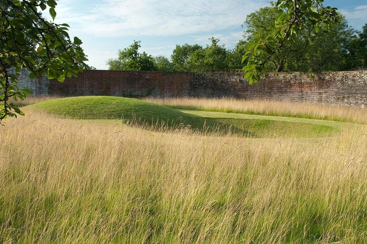 Intriguing and artistic mowed mound and depression in garden on Thames in Oxfordshire, designed by Dan Pearson.