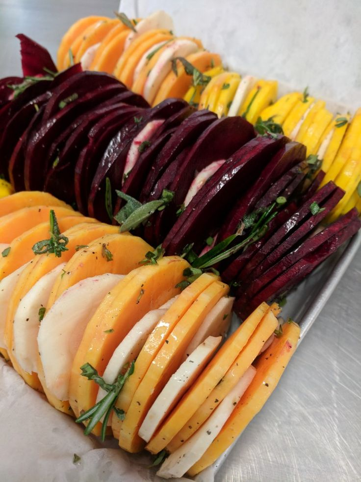 Herb roasted vegetable slices - red beets, golden beets, turnips, and butternut squash with fresh rosemary, sage, and thyme.