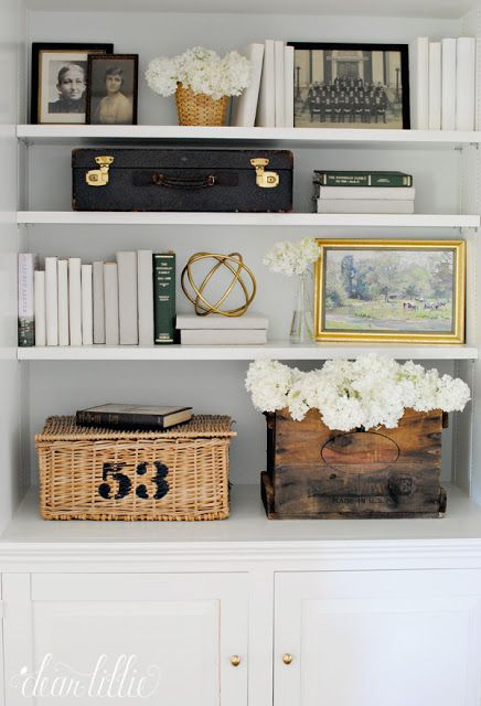 You can fill bookshelves with more than just books! Old family photos, artwork, baskets and even some sculptural pieces like this gold orb from HomeGoods help add personality and interest to these shelves. (Sponsored pin)