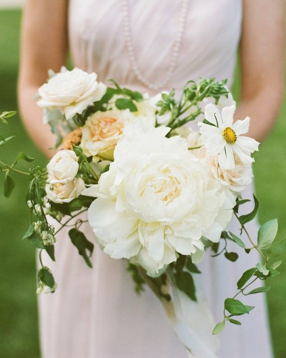 Each bridesmaid at this Utah celebration carried a mostly white bouquet, like this one featuring a large peony surrounded by roses, cosmos, and clematis vine.