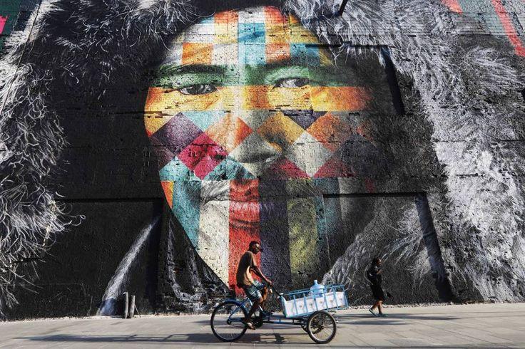 Un hombre en bicicleta pasa delante de un mural creado por Eduardo Kobra para decorar un edificio en el Distrito del Puerto, un área renovada antes de los Juegos Olímpicos de Río 2016.