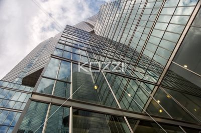 reflection on office blocks against cloudy sky. - Low angle shot of reflection of tall commercial building against cloudy sky.