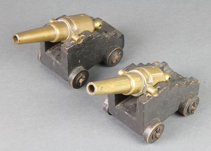 """Lot 215, A pair of 19th Century brass table top cannons with 6"""" drilled barrels, raised on wooden trunnions, est £40-60"""
