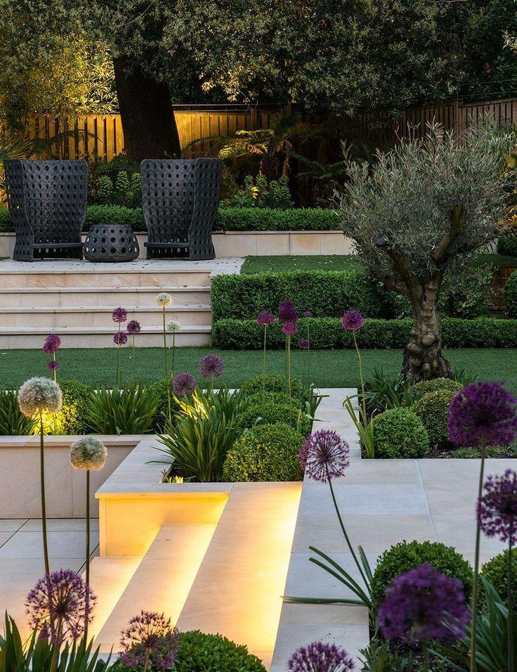Moderner Landschaftsgarten mit runden Hecken, mehreren Ebenen und Agapanthus. – Hausgarten Design
