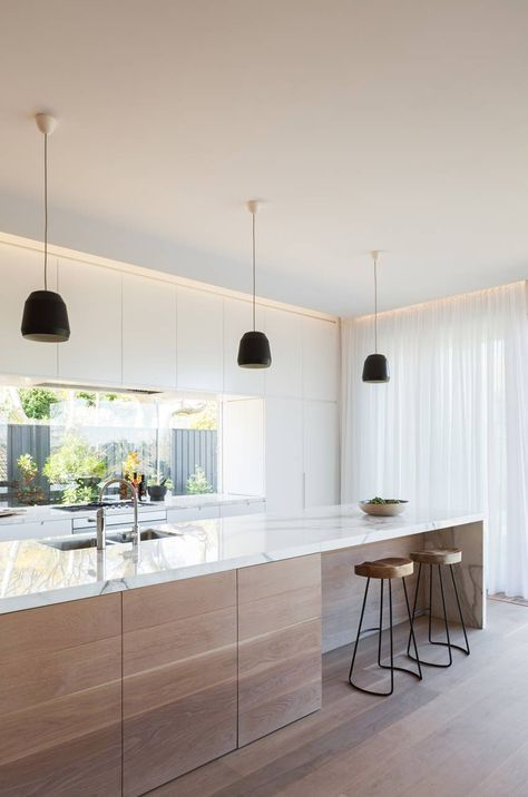 Cucina in classico stile scandinavo con mobili in quercia chiaro e piano in marmo bianco