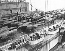 """Lockheed P-38 Lightning - Wikipedia - Cocooned Lockheed P-38 Lightnings & North American Aviation P-51 Mustangs line the decks of a U.S. Navy Escort """"Jeep"""" Carrier (CVE) ready for shipment to Europe from New York."""