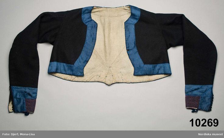 Kvinnotröja av mörkblå vadmal, kort modell, 2 framstycken /sidstycken och ett ryggstycke som går ned i en snibb mitt bak. Isydd svängd ärm med en söm, ärmsprund  7 cm långt, kantat med uddstansad vadmalsremsa och  knäppt med en hake och hyska. Hela tröjan kantad med klarblå 4,5 cm breda sideband som i framkantens nedre hörn och på ryggsnibben har litet blombroderi i sticksöm med blå silketråd i samma nyans som bandet. På ärmen även applikation innanför bandet av småmönstrat halvsiden i…