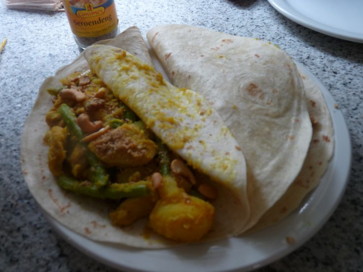 Surinaamse Roti;gekookte aardappel, gekookte boontjes, 2 uien in ringen, kipfilet, knoflook, koenjit, peper, zout, rozijnen, cashewnootjes, seroendeng met kokos, ketjap manis alles wokken en dan in de tortilla wraps inhoud: