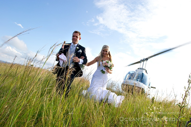 Bride and groom on mountain top with helicopter