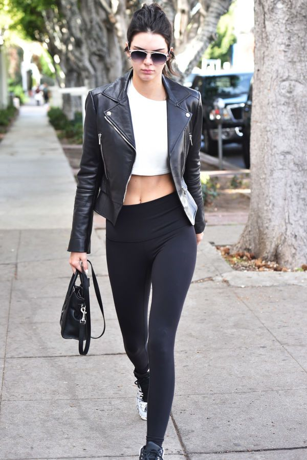 Kendall Jenner wears a white crop top, leggings, a moto jacket, and aviators