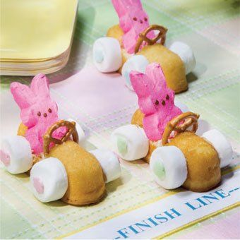 """Easter Bunny Racers Ingredients Large Marshmallows, cut horizontally Bunny Peeps® Mini pretzels Cream-Filled Cakes (e.g. Little Debbie® Cloud Cakes™) Decorator Icing Frosting Sprinkles Instructions Cut a small rectangle out of the top of the cream-filled cake about a third of the way back from the """"front"""". Use the white decorator icing to adhere the bunny Peep®, mini pretzel """"steering wheel"""" and large marshmallows in place. Decorate w/ frosting and sprinkles. Allow to set."""