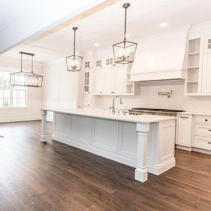 Large white kitchen with lantern style chandeliers/pendants