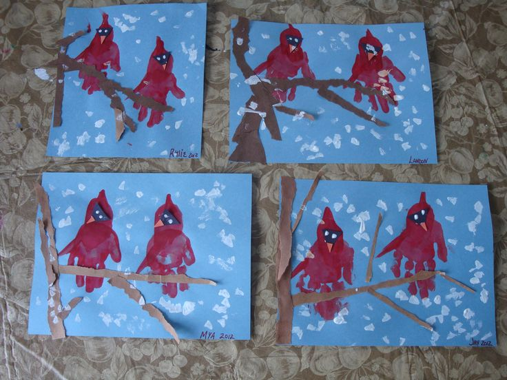 Clever handprint craft idea: Winter Cardinals. Cut out a black and orange triangle to create the face. Add brown torn paper to make the tree branches. Finish off with Qtip swabs of white painted snow.