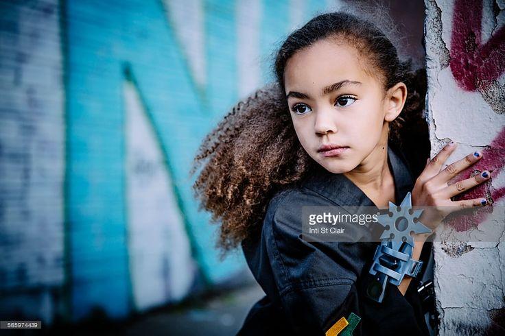 Mixed race girl in martial arts uniform with throwing star peeking around corner