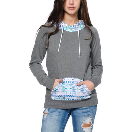 A multicolor tribal print hood and pocket contrasts the solid Grey body in the Larissa pullover hoodie from Empyre. This sweatshirt for women is made with a blended construction and a super soft fleece interior for ultimate comfort, while the long slim fi