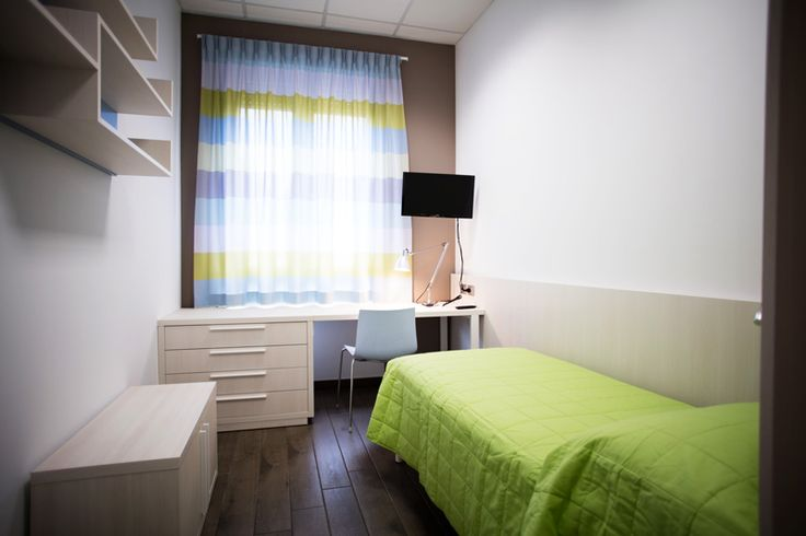 Arredo di una camera dello studentato di Pescara. L'essenzialità e la solidità degli arredi creano un effetto di modernità e luminosità.