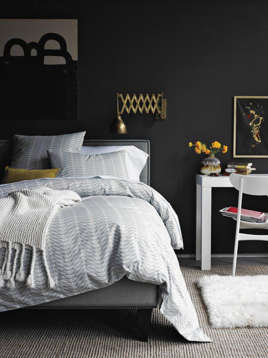 Dark and moody bedroom with charcoal paint and light neutral bedding. Metal accents and cozy knits.