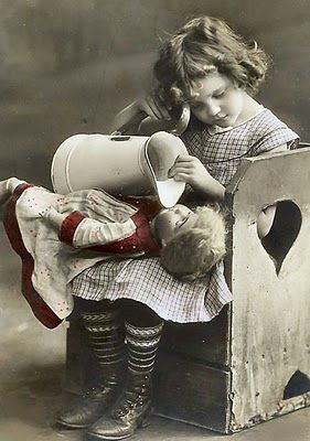 Vintage photo of a little girl with her doll, opting to forego the baby bottle.  This one made me laugh! ~*~