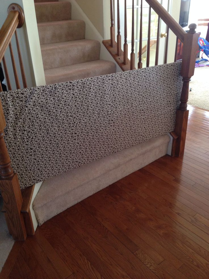 Home made baby gate using plywood cut to size, quilt bunting and fabric. So easy.