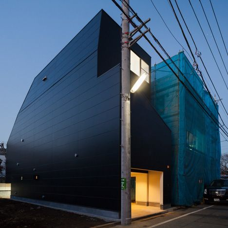 Level Architects squeezed this all-black house onto a narrow plot in Tokyo, adding sloping offset walls to protect residents' privacy.