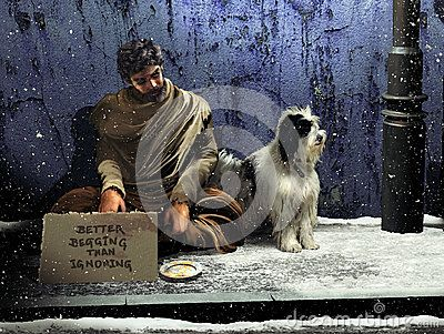 Beggar and his dog, sitting on the sidewalk at night, under the falling snow. The beggar exhibits a piece of cardboard with the inscription: Better begging than ignoring.  French proverb that illustrates the actual situations all over the world, where rich people ignore the necessities of the big majority, without realizing that there is more honor to beg, than to ignore the needs of others.
