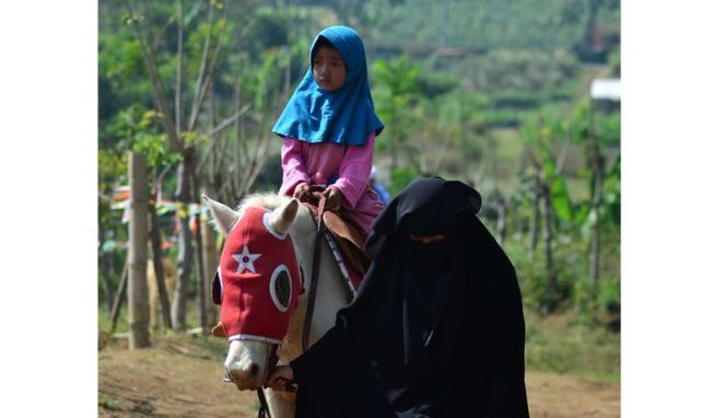 Pesantren Unik, Santri Wanitanya Ajari Memanah dan Berkuda = Sejumlah santri wanita pondok pesantren An Nashr mengajarkan cara menunggang kuda kepada siswa SD di Desa Giripurno, Kota Batu, Malang.