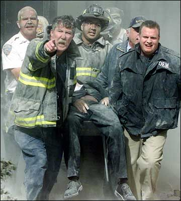 Rescue workers remove a man from the World Trade Center tower in New York City early September 11, 2001. Both towers were hit by planes crashing into the building. Victims of the attack — many suffering from extensive burns — began arriving at hospitals in New York City about an hour after two planes slammed into the twin towers. (REUTERS/Shannon Stapleton)