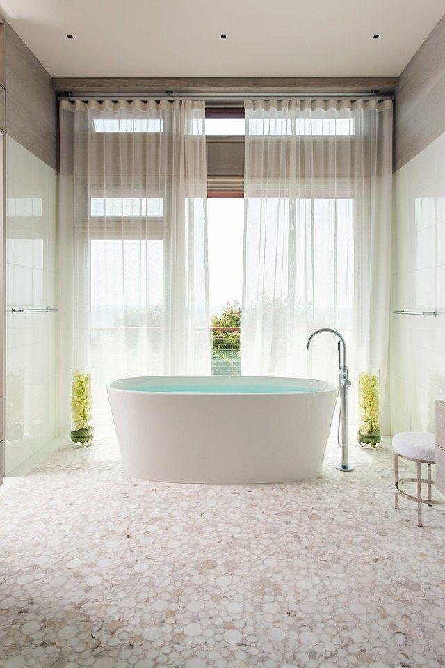carrelage de salle de bains à motifs ronds et baignoire îlot