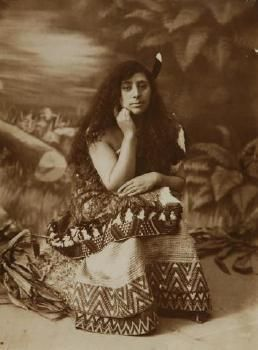 portrait of a young Maori woman, seated, in traditional dress,